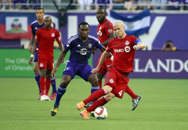 Apr 26, 2015; Orlando, FL, USA; Toronto FC midfielder Michael Bradley (4) and Orlando City SC midfielder/defender Amobi Okugo (5) fight to control the ball during the first half at Orlando Citrus Bowl Stadium. Mandatory Credit: Kim Klement-USA TODAY Sports