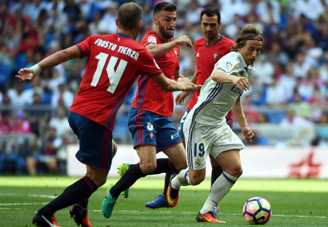 Real Madrid's Croatian midfielder Luka Modric (R) vies with Osasuna's defender Oier Mate (C) during the Spanish league football match Real Madrid CF vs CA Osasuna at the Santiago Bernabeu stadium in Madrid on September 10, 2016. / AFP / GERARD JULIEN (Photo credit should read GERARD JULIEN/AFP/Getty Images)